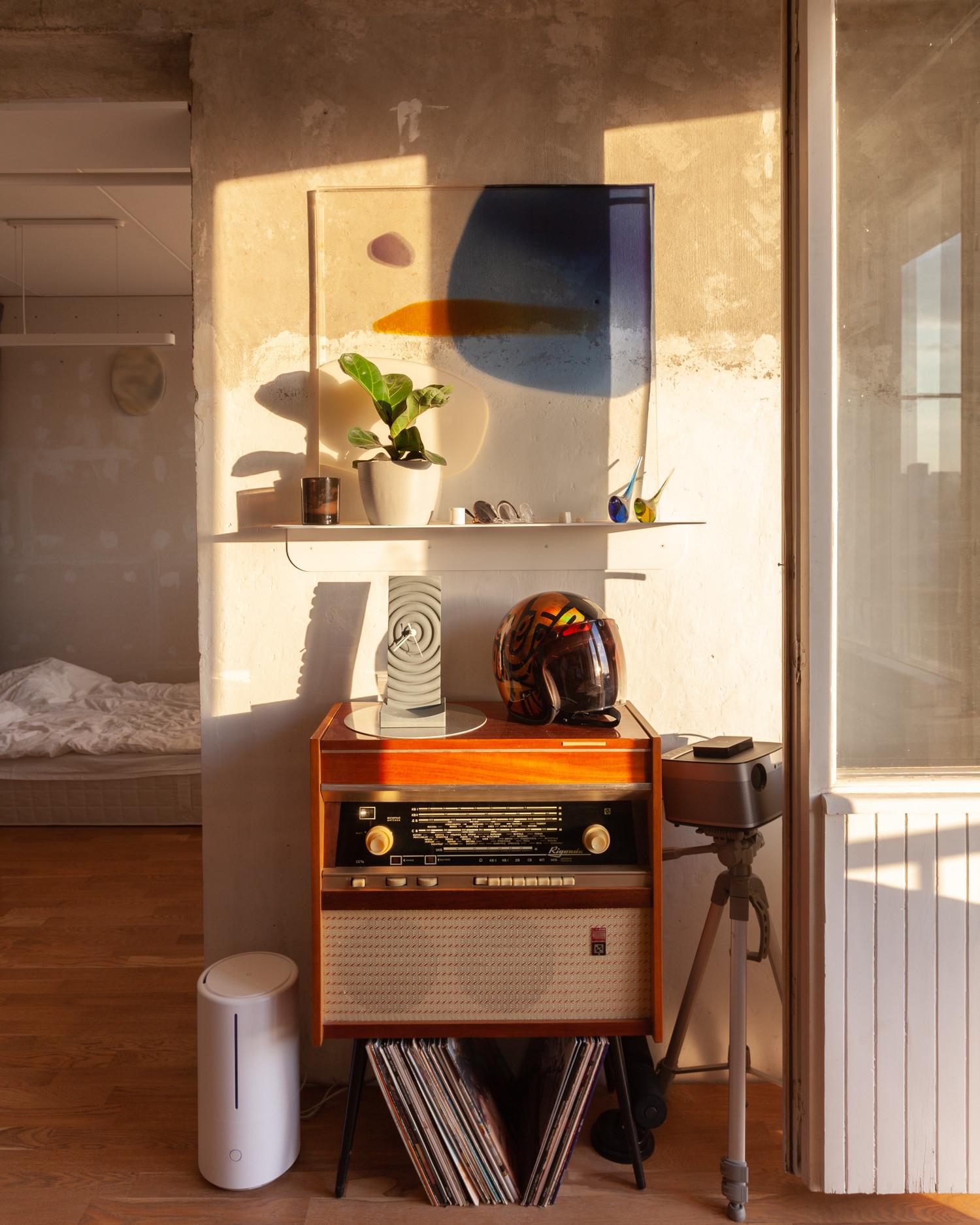 Радиола 'Ригонда' досталась от бабушки в рабочем состоянии. Часы, полка и растения куплены опять же через рекламу в инстаграме, а прозрачную картину сделала на заказ в цветах моей квартиры архитектор и художник Алиса Спотс.
