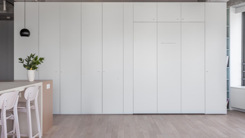 В квартире много шкафов, но все они встраиваемые и почти незаметные. А дополнительное спальное место в гостиной спрятано в шкаф.