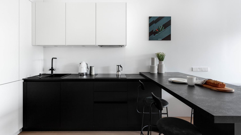 Белые шкафы сливаются со стеной. Кухонный фартук встроен в стену, заподлицо с поверхностью. Г-образная композиция черных кухонных баз и остров зонируют пространство.